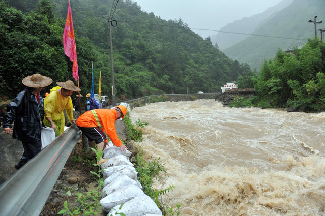 Workers use sandbags to reinforce a river bank amid high water levels caused by Typhoon Chan-Hom in Lin'an city in eastern China's Zhejiang province Saturday, July 11, 2015. A typhoon with wind gusts up to 125 miles per hour is headed toward China's southeastern coast. Officials say some 865,000 people have been evacuated from coastal areas of Zhejiang province. (Photo by Chinatopix via AP Photo)