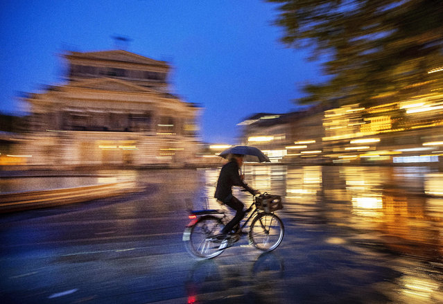 A man with umbrella rides his bike in front of the Old Opera in Frankfurt, Germany, on a rainy Monday, September 23, 2019. (Photo by Michael Probst/AP Photo)