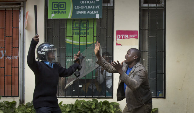 An opposition supporter pleads with a riot policeman, after being beaten with a wooden club by one then managing to escape but then being cornered by another, during a protest in downtown Nairobi, Kenya Monday, May 16, 2016. (Photo by Ben Curtis/AP Photo)