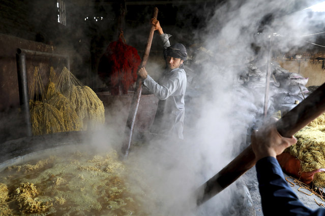 Laborers stir a vat of wool at a dyeworks, in Kabul, Afghanistan, Tuesday, October 1, 2019. The yarn will be used in making hand-knotted carpet. (Photo by Ebrahim Noroozi/AP Photo)