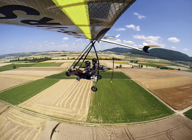 Toni Roth flies with his microlight aircraft over a field at the airfield in Schaffhausen, Switzerland, July 15, 2015. After a ban over 30 years, microlights are allowed to take off again in Switzerland. (Photo by Ennio Leanza/EPA)