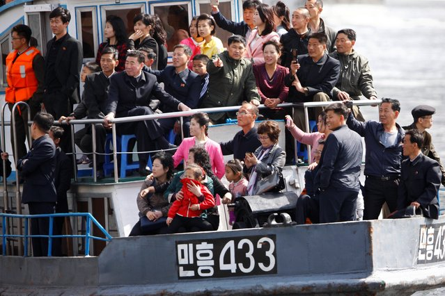 North Koreans tour on a vessel on the Yalu river outside Sinuiju, North Korea, opposite the Chinese border city of Dandong, in Liaoning province, China during the Labor Day holiday, May 1, 2019. (Photo by Jacky Chen/Reuters)