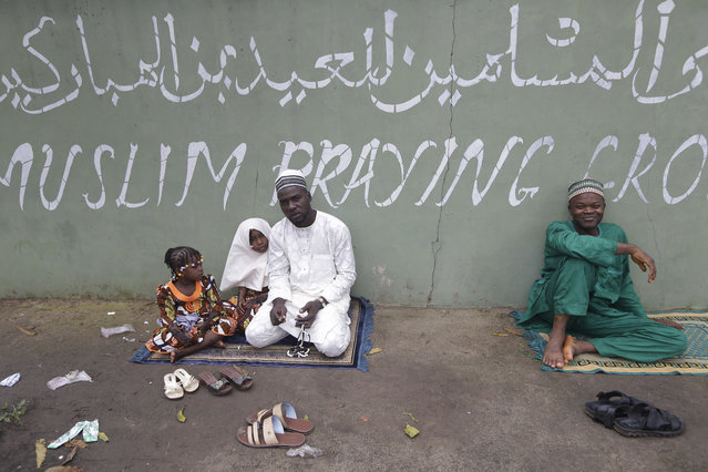 A Nigeria Muslim and his children attend Eid al-Fitr prayer in Lagos, Nigeria, Friday, July 17, 2015, marking the end of the Muslim holy fasting month of Ramadan. (Photo by Sunday Alamba/AP Photo)