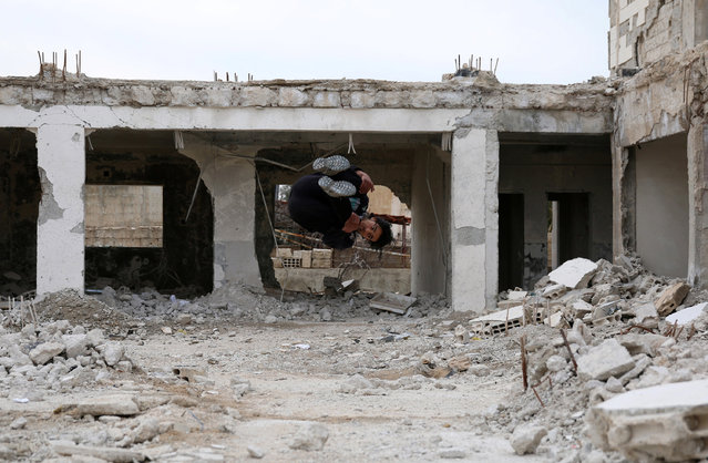 Parkour coach Ibrahim al-Kadiri, 19, demonstrates his Parkour skills amid damaged buildings in the rebel-held city of Inkhil, west of Deraa, Syria, February 4, 2017. Ibrahim and his team members say the sport is a challenge against the bad conditions they have to endure because of the war. (Photo by Alaa Al-Faqir/Reuters)