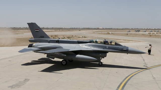 Iraq's Defence Minister Khaled al-Obeidi (L) sits in a F-16 fighter jet, during an official ceremony to receive four of these aircrafts from the U.S., at a military base in Balad, Iraq, July 20, 2015. (Photo by Thaier Al-Sudani/Reuters)