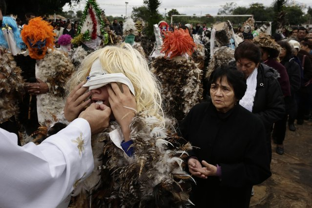 A Catholic parishioner receives Communion bread during a Mass marking the feast day of St. Francisco Solano, in Emboscada, Paraguay, Friday, July 24, 2015. (Photo by Jorge Saenz/AP Photo)