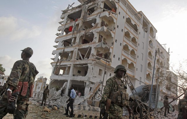 An African Union (AU) soldier walks past the scene of destruction following a suicide car bomb attack in the capital Mogadishu, Somalia Sunday, July 26, 2015. (Photo by Farah Abdi Warsameh/AP Photo)