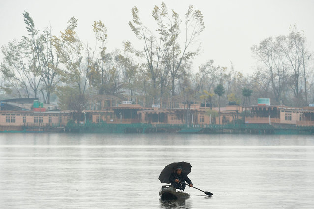 A Kashmiri man rows a boat in the waters of Dal Lake as it rains in Srinagar on November 22, 2019. (Photo by Tauseef Mustafa/AFP Photo)