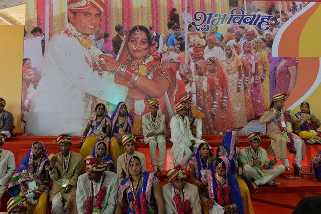 Indian brides and grooms wait for the start of a mass wedding in New Delhi on June 15, 2014. Some 92 low-income and disabled couples tied the knot in a free mass wedding ceremony organised by the non-profit organisation Narayan Sewa Sansthan. (Photo by Chandan Khanna/AFP Photo)