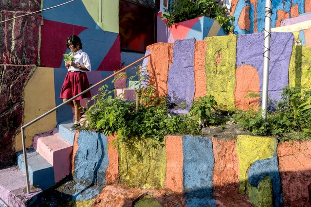 """This picture taken on May 23, 2017 shows a village girl walks along a path at an Indonesian hamlet dubbed """"the rainbow village"""" in Semarang, central Java, that has become an internet sensation and attracting hordes of visitors. (Photo by Suryo Wibowo/AFP Photo)"""