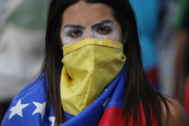 In this Wednesday, January 23, 2019, an anti-government protester covers her face with a Venezuelan flag, and uses toothpaste around her eyes to help lessen the effect of tear gas, during clashes with security forces after a rally demanding the resignation of President Nicolas Maduro in Caracas, Venezuela. The head of Venezuela's opposition-run congress declared himself interim president at the rally, until new elections can be called. (Photo by Fernando Llano/AP Photo)