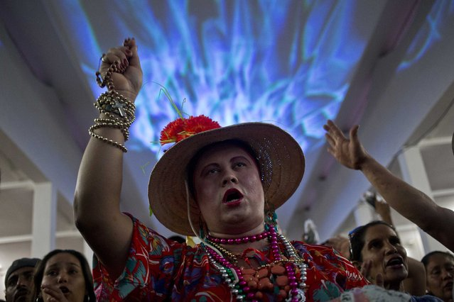 "A  man wears a dress of the ""La vieja del puro"" folk dance and sings during the celebration in honor of the Managua's patron saint, Santo Domingo de Guzman, in Managua, Nicaragua, Saturday, August 1, 2015. Promise keepers dance inside the church along with the image of the saint as a way to pay a promise made for a perceived miracle or answer to their prayers. (Photo by Esteban Felix/AP Photo)"