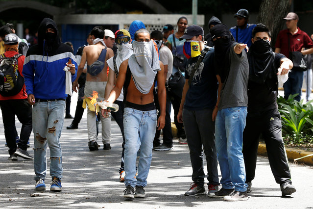 Demonstrators gather as they clash with riot police officers during a protest called by university students against Venezuela's government in Caracas, Venezuela, June 9, 2016. (Photo by Carlos Garcia Rawlins/Reuters)