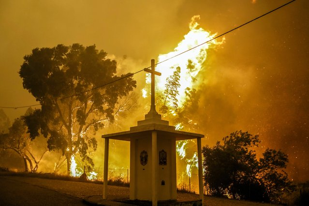 Flames rise next to a church during a fire in Pampilhosa da Serra, central of Portugal, 18 June 2017. At least sixty two people have been killed in forest fires in central Portugal, with many being trapped in their cars as flames swept over a road on the evening of 17 June 2017. (Photo by Paulo Novais/EPA)