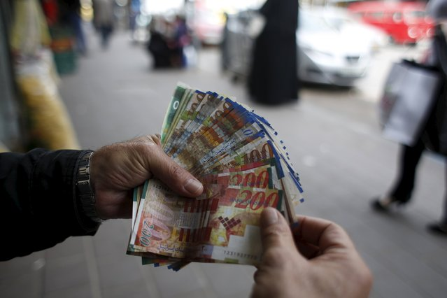 A Palestinian money exchanger displays money at a market in the West Bank city of Ramallah March 25, 2015. Israel's decision to withhold $130 million a month in revenue collected on behalf of the Palestinians is strangling the economy and leaving the banking system dangerously exposed, the Palestinian central bank governor said. (Photo by Mohamad Torokman/Reuters)