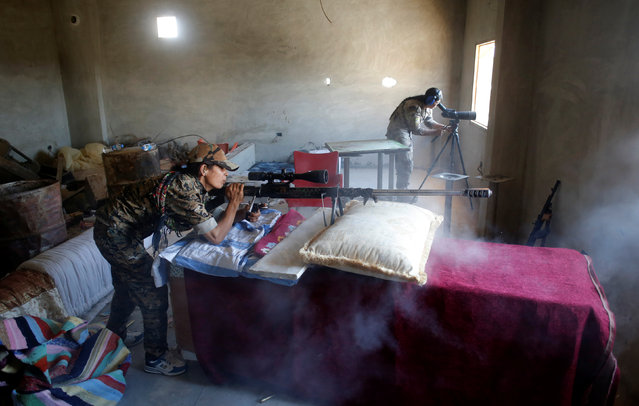 A female Kurdish fighter from the People's Protection Units (YPG) fires a long range sniper rifle at Islamic State militants in Raqqa, Syria June 18, 2017. (Photo by Goran Tomasevic/Reuters)