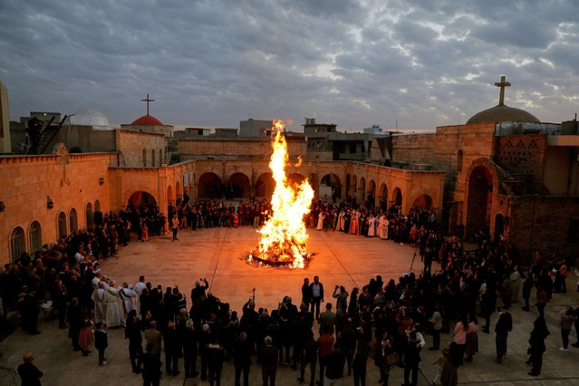 Iraqi Christians gather around a fire as they attend a mass on Christmas Eve at the Grand Immaculate Church in al-Hamdaniya, near Mosul, Iraq, December 24, 2019. (Photo by Abdullah Rashid/Reuters)