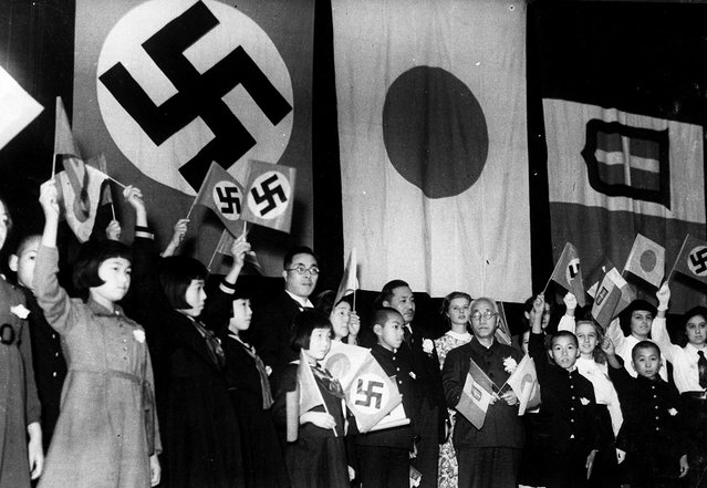 Children of Japan, Germany, and Italy meet in Tokyo to celebrate the signing of the Tripartite Alliance between the three nations, on December 17, 1940. Japanese education minister Kunihiko Hashida, center, holding crossed flags, and Mayor Tomejiro Okubo of Tokyo were among the sponsors