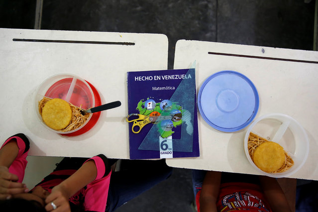 "A math book that reads ""Made in Venezuela"" is seen next to meal boxes during lunch break at an improvised classroom in a communal house, which is part of state school Monsenor Marco Tulio Ramirez Roa, in La Fria, Venezuela June 2, 2016. (Photo by Carlos Garcia Rawlins/Reuters)"