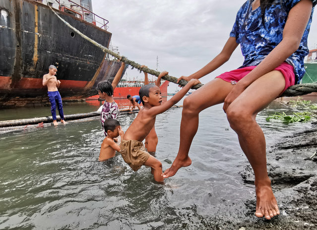 Filipino children frolic next to ships taking shelter inside a seaport in Navotas city, north of Manila, Philippines, 27 August 2019. According to the latest advisory from Philippine Atmospheric Geophysical and Astronomical Services Administration (PAGASA), Tropical Storm Podul intensified from a tropical depression into a tropical storm on August 27, while moving toward Central Luzon with a maximum winds of 65 kilometers per hour and gustiness of up to 80 km/h. (Photo by Francis R. Malasig/EPA/EFE)