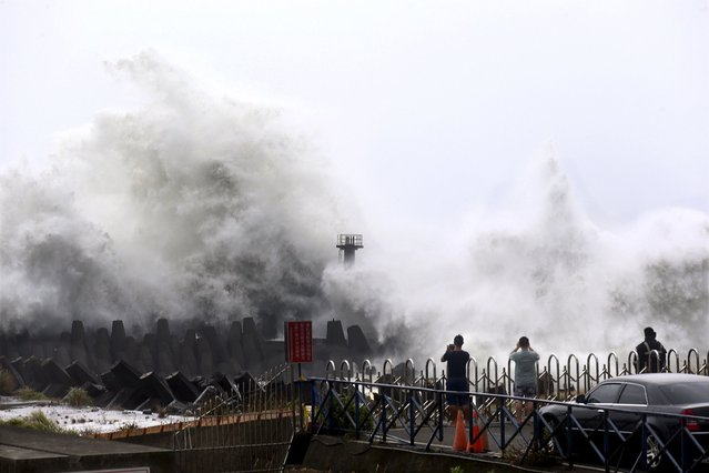 People take pictures at waves as Typhoon Soudelor approaches the northeastern coastal town of Nanfangao in Ilan county, northern Taiwan, August 7, 2015. (Photo by Jerry Chen/Reuters)