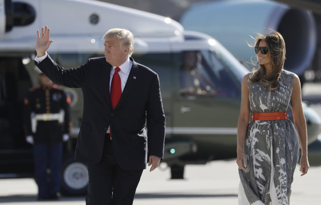 President Donald Trump, with first lady Melania Trump, waves as they walk from Marine One before boarding Air Force One in Hamburg, Germany, Saturday, July 8, 2017, as they head to Washington following the G20 Summit. (Photo by Evan Vucci/AP Photo)