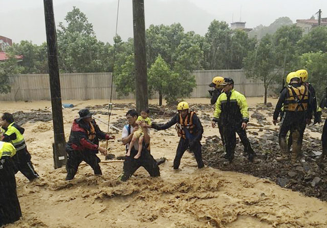 In this image released by the New Taipei Fire Department, emergency rescue personnel carry a child through a flash mudslide caused by Typhoon Soudelor in Xindian, New Taipei City, northern Taiwan, Saturday, August 8, 2015. At least four people were killed and four were missing when powerful Typhoon Soudelor slammed into Taiwan, authorities said Saturday. (Photo by New Taipei Fire Department via AP Photo)