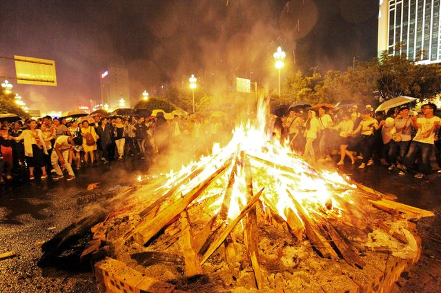 Local ethnic Yi minority residents and visitors surround a fire as they celebrate the Torch Festival during a rainfall in Xichang, Sichuan province, August 8, 2015. Thousands of people took part in the annual celebration on Saturday which originated from a legend that an ethnic Yi hero earned harvest for his folks by leading them to kill off pests with fire in the ancient time. (Photo by Reuters/Stringer)