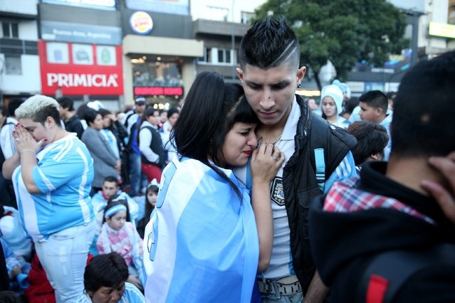 Argentine soccer fans listen to a broadcast of the second half of the World Cup final on July 13, 2014 in Buenos Aires, Argentina. (Photo by Joe Raedle/Getty Images)