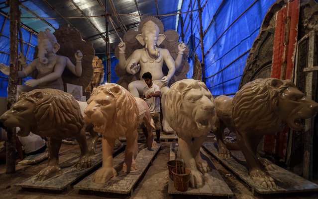 "An Indian artist gives the final touch to lion sculptures as he stands in front of idols of elephant headed Hindu God Ganesha at a workshop in Mumbai, India, August 12, 2015. The upcoming festival marks the birthday of Lord Ganesha. During the event, Ganesha idols are worshipped at hundreds of ""pandals"" or makeshift tents before they are immersed into water bodies. (Photo by Divyakant Solanki/EPA)"