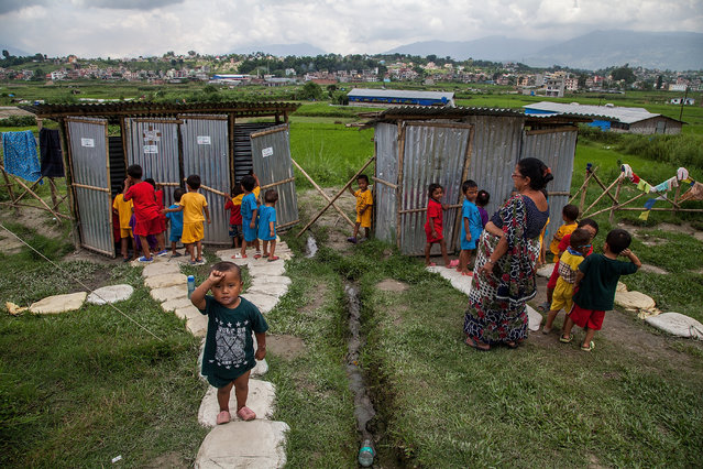 Children line up to go to the toilet during a break from classes in the Bode displacement camp on August 13, 2015 in Bhaktapur, Nepal. There are 1,087 people living in the displacement camp in Bode, Bhaktapur, all of whom have lost their homes in Sindupalchowk district, one of the worst affected areas by the earthquake that hit Nepal, and are currently being supported by NGOs. (Photo by Omar Havana/Getty Images)