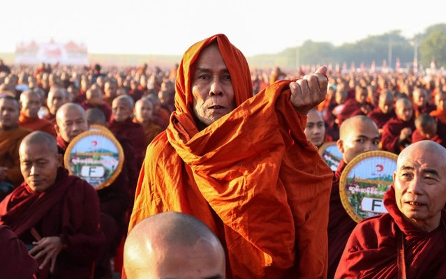 Monks line up for alms during the alms-giving ceremony to 30,000 monks organize by the region government of Mandalay affiliated with Dhammakaya Foundation at Chanmyathazi Airport in Mandalay on December 8, 2019. Thirty-thousand monks assembled in the early morning chill of Mandalay for a spectacular alms-giving event involving a controversial mega-temple under scrutiny across the border in Thailand. (Photo by Kyaw Zay Win/AFP Photo)