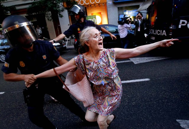 A demonstrator is detained by the police office during a protest against austerity measures announced by the Spanish government, in front of the Popular Party in Madrid on July 13, 2012