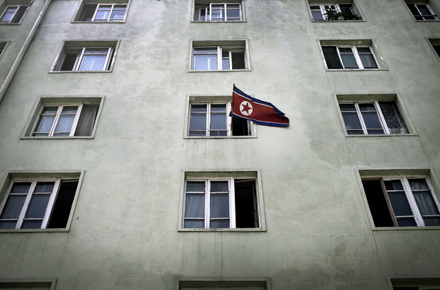 A North Korean national flag is hung out of a window of an apartment building, Sunday, July 27, 2014, in Pyongyang, North Korea. North Koreans gathered at Kim Il Sung Square Sunday as part of celebrations for the 61st anniversary of the armistice that ended the Korean War. (Photo by Wong Maye-E/AP Photo)