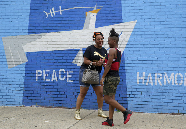 Women chat in the Penn North neighborhood of Baltimore, Thursday, June 23, 2016, near the site of unrest following the funeral of Freddie Gray. Officer Caesar Goodson, one of six Baltimore city police officers charged in connection to the death of Gray, was acquitted of all charges in his trial Thursday. (Photo by Patrick Semansky/AP Photo)