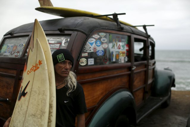 A surfer waits before attending a protest against the death of a cyclist by a car, in Lima, Peru, August 22, 2015. The protestors demanded more respect for cyclists from motorists, as well as more bicycle paths from the city government. Surfers and cyclists gathered to remember a friend who was killed when he was riding his bicycle towards the beach a week ago. (Photo by Pilar Olivares/Reuters)