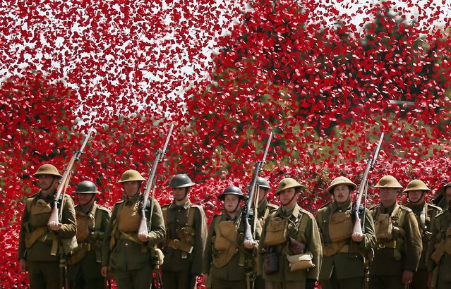 Members of the Great War Society living history group dressed as 4th Battalion the Middlesex Regiment stand under a shower of a million poppy flowers representing the dead during a World War One centenary ceremony at the Tank Museum, Bovington on August 4, 2014 in England. (Photo by Peter Macdiarmid/Getty Images)