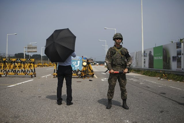 A journalist stands next to a South Korean soldier standing guard as he waits for vehicles transporting a South Korean delegation at a checkpoint on the Grand Unification Bridge, which leads to the truce village Panmunjom, just south of the demilitarized zone separating the two Koreas, in Paju, South Korea, August 24, 2015. (Photo by Kim Hong-Ji/Reuters)
