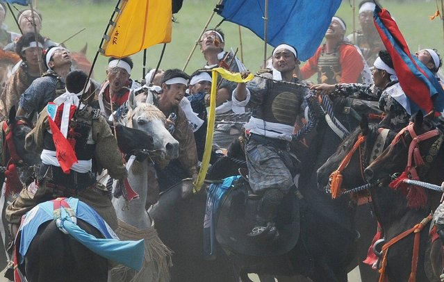 """Local people in samurai armor ride their horses as they try to catch a yellow sacred flag (C) at the annual Soma Nomaoi Festival in Minamisoma, Fukushima Prefecture, on July 29, 2012. Some 400 horses and thousands of people took part in the 1,000-year-old """"Soma Nomaoi"""", or wild horse chase, at the weekend in the shadow of Japan's crippled Fukushima nuclear plant. (Photo by Toru Yamanaka/AFP Photo)"""