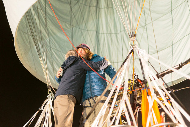 Russian adventurer Fedor Konyukhov hugs a member of his support staff as he prepares to leave in his balloon for his attempt to break the world record for a solo hot-air balloon flight around the globe near Perth, Australia, in this handout image received July 12, 2016. (Photo by Oscar Konyukhov/Reuters)