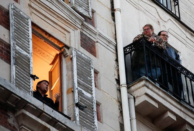 French tenor singer Stephane Senechal sings from his apartment window in Paris as a lockdown is imposed to slow the rate of the coronavirus disease (COVID-19) spread in France, March 24, 2020. (Photo by Gonzalo Fuentes/Reuters)