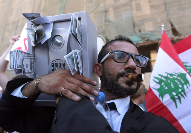 A Lebanese anti-government protester acts the role of a Lebanese politician holding a safe with fake money sticking out, during a demonstration against the trash crisis and government corruption, in downtown Beirut, Lebanon, Saturday, August 29, 2015. (Photo by Bilal Hussein/AP Photo)