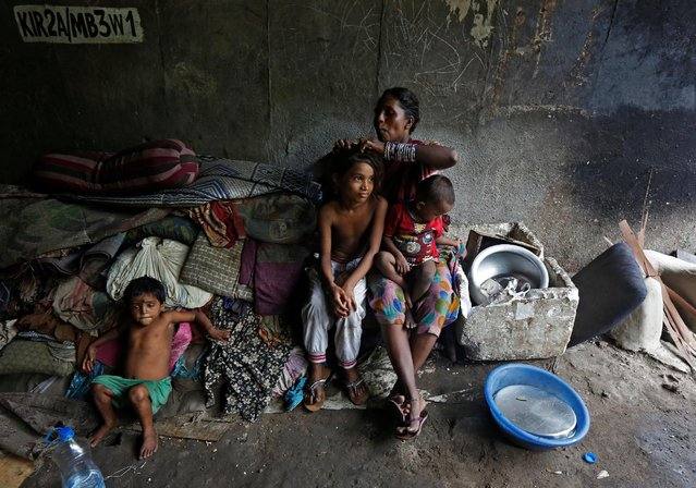 A woman searches for lice in her daughter's hair outside their makeshift home under a flyover in Kolkata, India, July 20, 2016. (Photo by Rupak De Chowdhuri/Reuters)