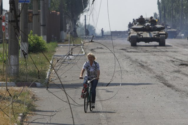 A local resident riding a bicycle is pictured through damaged power lines while a Ukrainian tank (rear) patrols the area in the eastern Ukrainian town of Vuhlehirsk August 14, 2014. (Photo by Valentyn Ogirenko/Reuters)