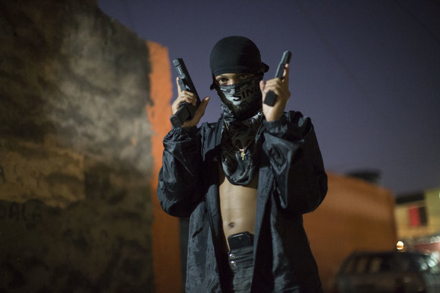 In this July 11, 2016 photo, a young, masked drug trafficker poses for photos holding his guns at a slum in Rio de Janeiro, Brazil. Teenagers openly tote guns while they work as guards, lookouts and distributors for drug lords operating just a few miles from where hundreds of thousands and tourists and athletes will be for the Aug. 5-21 Olympic Games. (Photo by Felipe Dana/AP Photo)