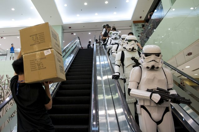 A store staff carries boxes as actors dressed up as Stormtrooper take an escalator before the launch of the film's new toys in Hong Kong, China, September 3, 2015. (Photo by Tyrone Siu/Reuters)