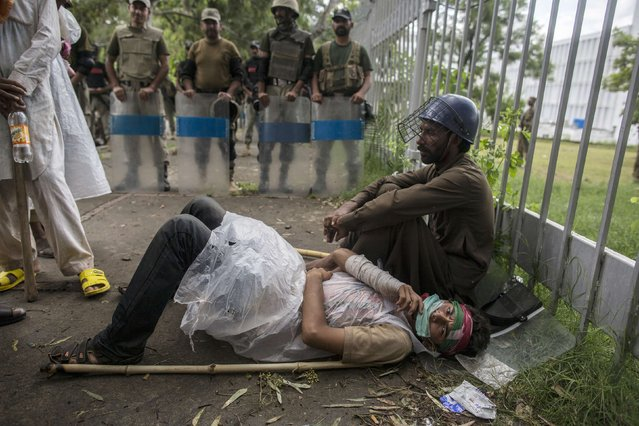 A supporter of Tahirul Qadri lies on the ground while soldiers block a road leading to the prime minister's house in Islamabad, on September 1, 2014. (Photo by Zohra Bensemra/Reuters)