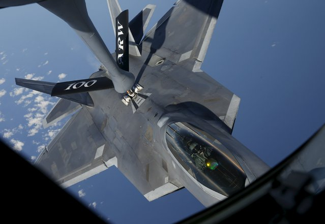 A F-22 Raptor fighter jet of the 95th Fighter Squadron from Tyndall, Florida is seen during refuelling by a KC-135 Stratotanker from the 100th Air Refueling Wing at the Royal Air Force Base in Mildenhall in Britain as they fly over the Baltic Sea towards Spangdahlem airbase, Germany September 4, 2015. (Photo by Wolfgang Rattay/Reuters)