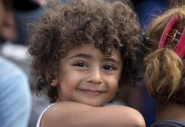 A migrant child smiles as his family waits to board a train after crossing the Macedonian-Greek border near Gevgelija, Macedonia, September 6, 2015. (Photo by Stoyan Nenov/Reuters)