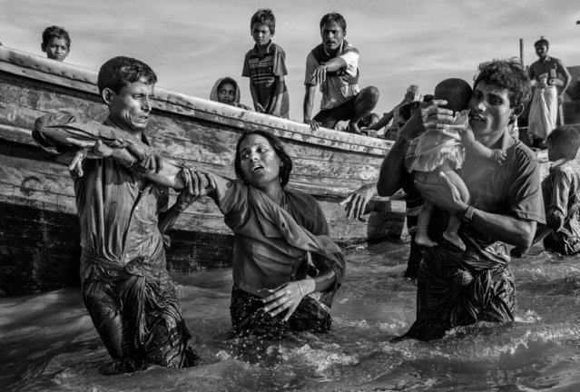 A Rohingya refugee woman is helped from a boat as she arrives exhausted on the Bangladesh side of the Naf River at Shah Porir Dwip after fleeing her village in Myanmar, on October 1, 2017 in Cox's Bazar, Bangladesh. (Photo by Kevin Frayer/Getty Images)
